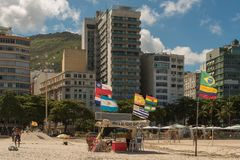 Buildings in Front of the Copacabana Beach. Rio de Janeiro, Brazil - February 1, 2018: Beach tent with country flags in the wind and apartment buildings in front stock photo