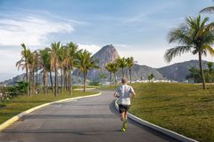 Man running at Marina da Gloria track and Sugar Loaf Mountain on background - Rio de Janeiro, Brazil. Rio de Janeiro, Brazil - Oct 25, 2017: Man running at royalty free stock photo