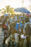 Rio de Janeiro Sunset Carnival Crowd. RIO DE JANEIRO, BRAZIL - FEBRUARY, 2015: Crowds of people wearing carnival gear gather along Ipanema Beach for a street Stock Photo
