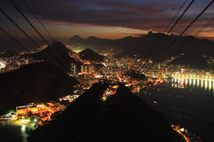 Rio de Janerio gondola city night sunset. Night, evening view from sugar loaf mountain of the cable car and Rio de janerio bay as sun sets over the city Royalty Free Stock Photo