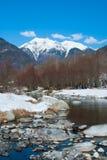 Rio de Sarca com bancos cobertos de neve e as montanhas nevados foto de stock