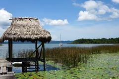 Rio Dulce. Wooden pier and cruising sailboat at anchor in a small bay overgrown with reeds and water lilies in Rio Dulce. Guatemala Royalty Free Stock Images