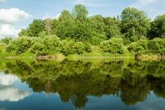 Rio e seus bancos Árvores ao longo de ambos os lados da água O céu é nebuloso Fotografia de Stock
