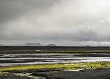 Rio glacial no deserto preto da areia com vegetação verde-clara do musgo nas montanhas de Islândia, Europa imagens de stock