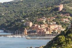 Rio Marina med den hamn- och klocka-torn Torre dell'orologioen, Elba, Tuscany, Italien Arkivbild