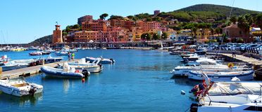 Rio Marina town, Elba island, card, Italy. Water, blue sea, rocks, waves and sea background, romantic landscape with sunrays on the rocks. Elba island royalty free stock photo