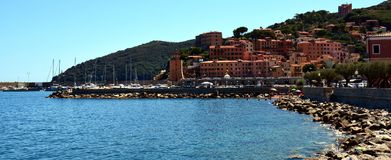 Rio Marina, town, Elba island, rocks and background. Rio Marina seen as a nice town, sea, waves, port, horizon, boats and Tyrrhenian sea, Italy, Livorno royalty free stock image