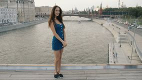 Rio modelo da ponte do suporte da mulher moreno que olha a câmera e o sorriso doce 4k video estoque