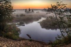 Rio na névoa, imediatamente antes do nascer do sol Um fulgor morno nas nuvens dos primeiros raios do sol fotos de stock royalty free