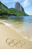 Rio 2016 Olympic Rings Message Drawn in Sand. RIO DE JANEIRO, BRAZIL - MARCH 20, 2015: Olympic rings drawn on smooth sand of Red Beach Praia Vermelha with a view Royalty Free Stock Photos