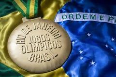 Rio 2016 Olympics Gold Medal on Brazil Flag. RIO DE JANEIRO, BRAZIL - FEBRUARY 3, 2015: Large gold medal commemorating the 2016 Jogos Olimpicos (Olympic Games) royalty free stock photo