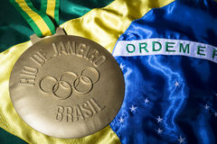 Rio 2016 Olympics Gold Medal on Brazil Flag. RIO DE JANEIRO, BRAZIL - FEBRUARY 3, 2015: Large gold medal commemorating the 2016 Olympic Games sits on Brazil flag royalty free stock image