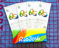 Rio 2016 Olympics tickets. Tickets to the closing ceremony of Rio 2016 Olympics in souvenir folder on blue and red terry clothe towel Stock Photos