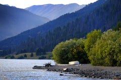 Rio ou lago com o barco na costa com montanhas imagens de stock