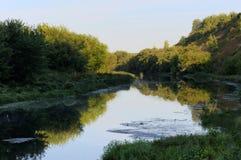 Rio pequeno quieto com as árvores verdes em ambos os bancos no início do verão Imagens de Stock Royalty Free