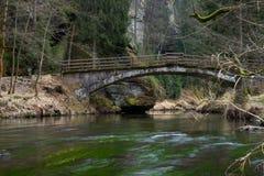 Rio quieto da mola na floresta com ponte velha imagem de stock