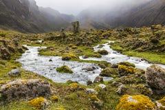 Rio, rochas e nuvens no vale de Collanes no vulcão do altar do EL Fotografia de Stock