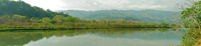 Rio Terraba Panorama. A panoramic view of a Costa Rican River near Potrero Grande, in the southern part of the country, with misty mountains in the distance Stock Photo