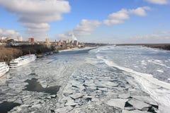 Rio urbano do inverno coberto com o gelo contra o céu azul com alguns fotos de stock