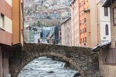 Rio Valira na opinião da ponte e das casas de Engordany em um dia da queda de neve na cidade pequena Escaldes-Engordany em Andorr foto de stock