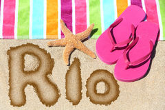 Rio written on beach sand with a colorful towel Royalty Free Stock Photos