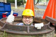 Rioleringsarbeider in het mangat Stock Afbeelding