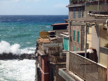 Riomaggiore Cinque Terre Italy waves breaking against historic h Stock Image