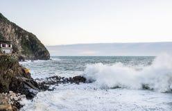 RIOMAGGIORE, ITALIE - 10, FÉVRIER Les grandes vagues pendant le jour orageux au village des pêcheurs de Riomaggiore en Cinque Ter Photographie stock libre de droits