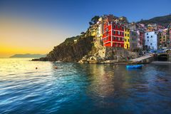 Riomaggiore town, cape and sea landscape at sunset. Cinque Terre National Park, Liguria Italy. Riomaggiore town, cape and sea landscape at sunset. Seascape in stock images