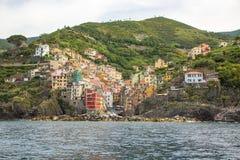 Riomaggiore, uma das cinco cidades pequenas no parque nacional de Cinque Terre Vista do navio da excursão imagens de stock royalty free