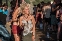 A beautiful young blonde woman dances on the main stage of the Lost Theory psytransce music festival in Riomalo de Abajo