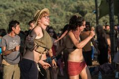 Young man and woman dance at sunset on the Lost Theory psytransce music festival held in Riomalo de Abajo