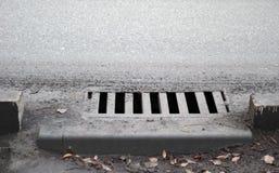 Riool door voetpad Het afvoerkanaal van de regenwaterstraat stock foto