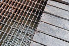 Riool roestig staal en de houten drainage van het dekkingswater Textuur en bac Stock Foto's