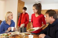Riordinare adolescente inutile dopo il pasto della famiglia fotografie stock libere da diritti