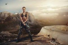 Riot girl on a rocky ledge with a gun Stock Photos