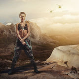 Riot girl on a rocky ledge with a gun royalty free stock photography