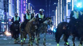 Riot officers on horses patrolling chaotic street stock video
