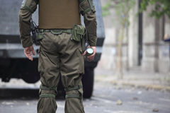 Riot Police in Chile. Riot police with tear gas bomb in his hands Stock Image