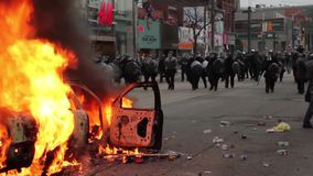 Riot police line walk towards crowd through fire stock video footage