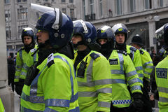 Riot Police at London Anti-Cuts Protest. Police in riot gear on standby in central London after violoent clashes with protesters during a large anti-cuts rally Stock Photos