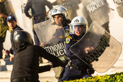 Riot police with their shield, take cover during a rally in front of the Athens University Stock Photography