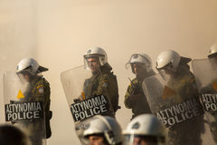 Riot police with their shield, take cover during a rally in front of Athens University, Stock Image