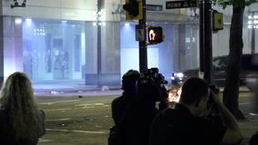 Riot police truck rolling with burning trashcan. Riot officers standing in crowd at night with unmarked police truck patrolling and burning trash can in the city stock video