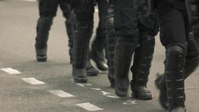 Riot police walking on road.
