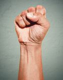 Riot protest fist raised in the air. Male clenched fist on dark grunge background. Royalty Free Stock Image