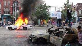 Rioters jump and set police cars on fire - HD 1080p stock video