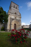 Rioux church with flowers. Facade of the romanesque Rioux church with red  roses in the forefront. Region of Charente in France Royalty Free Stock Photography