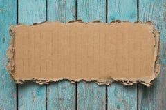 Rip cardboard piece on blue vintage wood background. Rip cardboard piece on blue wood background royalty free stock image