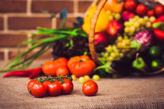 Rip cherry tomatoes on the branch. On the background fresh fruit. And vegetables mix. Warm toned. Horizontal Stock Photos